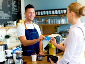 Una mujer paga con tarjeta en una cafetería