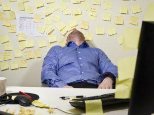 Un hombre se queda dormido con la pared llena de post its