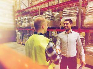 Un trabajador da la mano a uncomercial en una fábrica