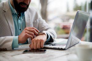 Un hombre consulta su reloj frente a su portátil