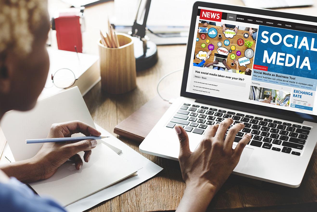 """Mujer frente a un portátil donde s epuede leer la palabra """"social media"""""""