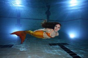 Una mujer vestida de sirena nada bajo el agua