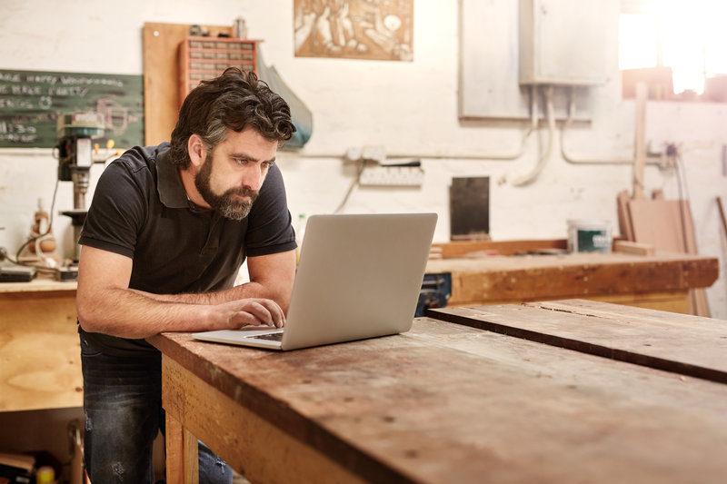 Bearded man who owns a small business, bending over at his work bench to type on his laptop, while working in his workshop and design studio