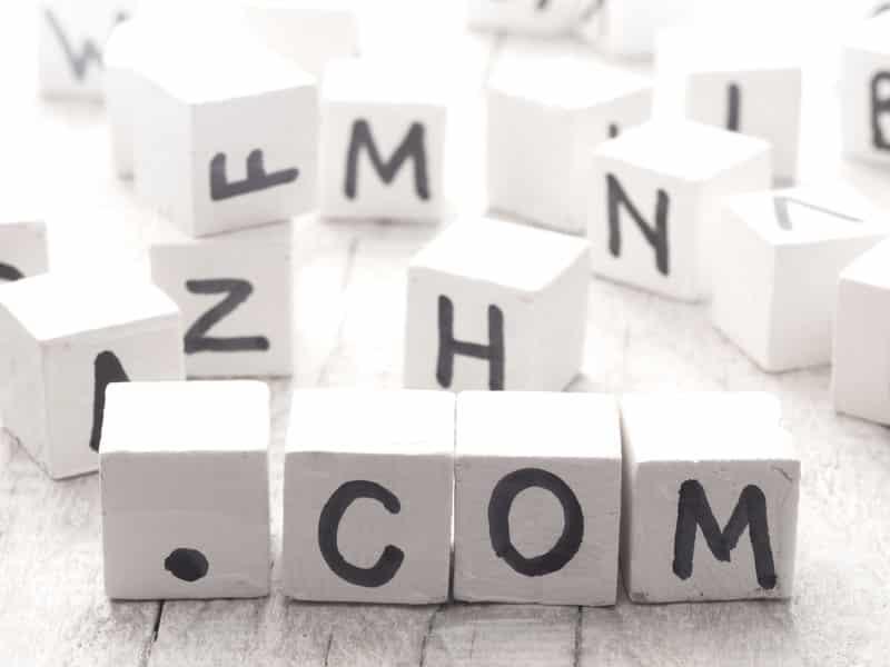 cubes blancs avec différentes lettres formant le signe .com