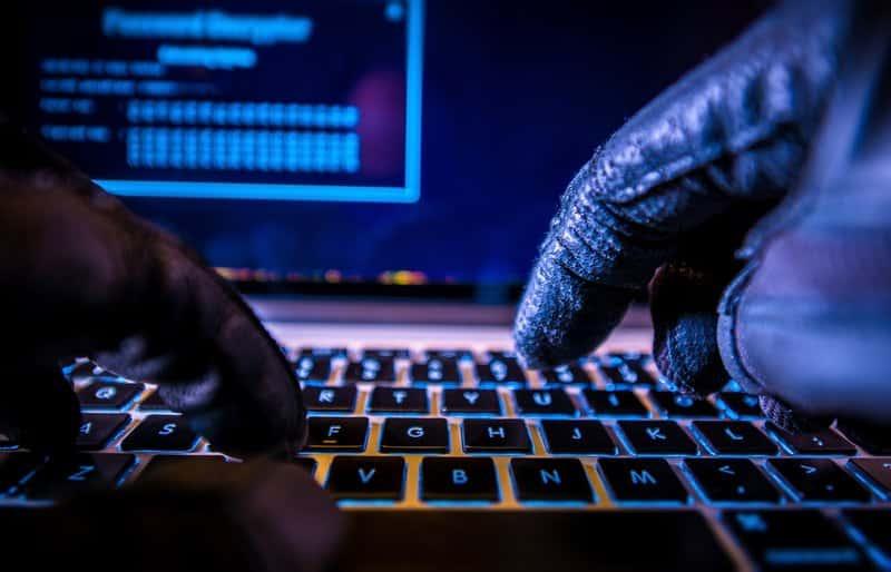 mains de hackers tapant sur le clavier d'un ordinateur éclairé par une lumière bleue