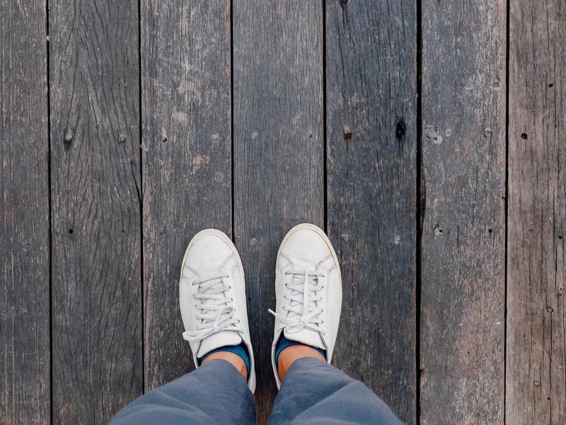 baskets blanches vues depuis le dessus sur un pont en bois pour illustrer le démarrage d'une entreprise