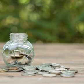 bocal en verre avec fissure qui laisse échapper des pièces de monnaie