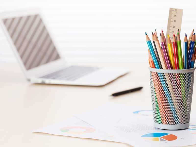 un pot de crayons de couleurs avec un ordinateur portable en arrière plan
