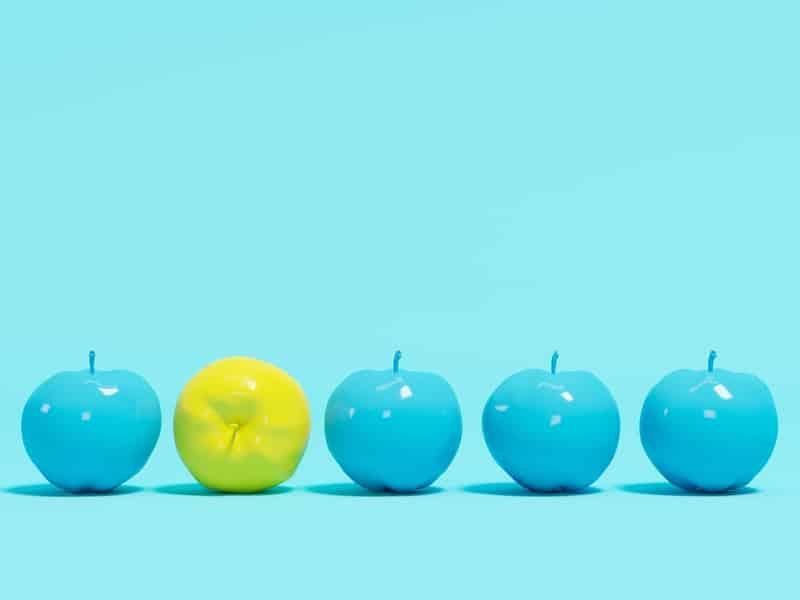 quatre pommes bleues et une pomme jaune qui illustre une idée ou un concept innovant