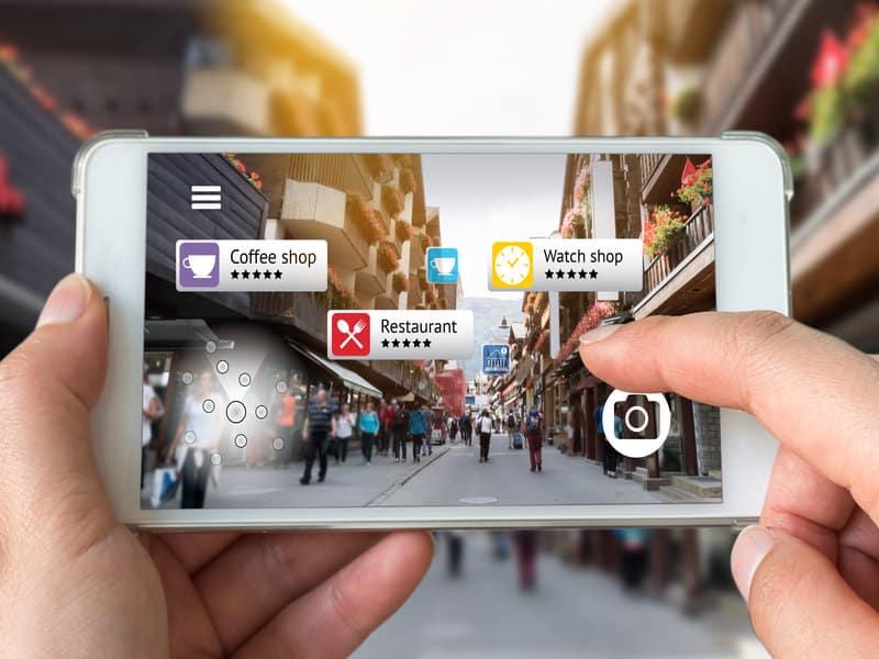 personne tenant un iphone avec effet de transparence et sur lequel on voit des emplacements et des revues de commerces de proximité
