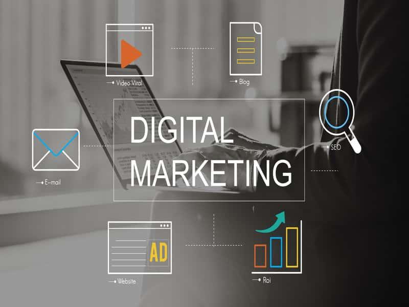 mots digital marketing écrit sur un fond noir blanc avec ordinateur et icones analytiques colorés tout autour