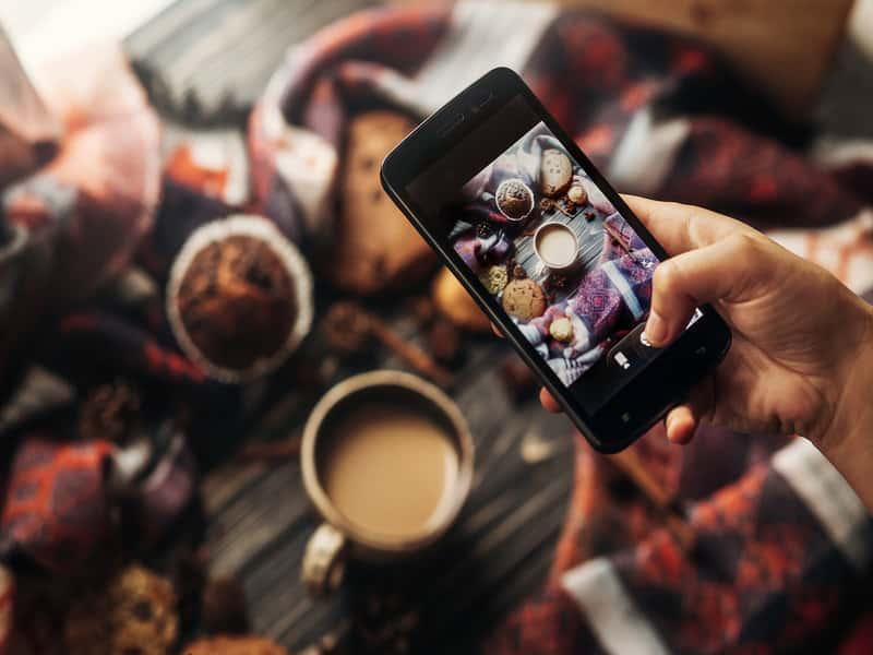 vue du dessus d'un iphone prenant une photo instagram d'un café et de nourriture