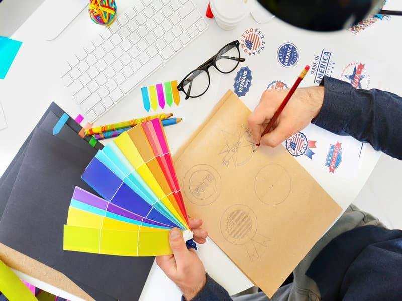 designer qui dessine un logo et tient une palette de couleurs