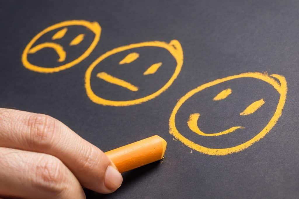main qui dessine à la craie des smileys orange représentant des clients satisfaits