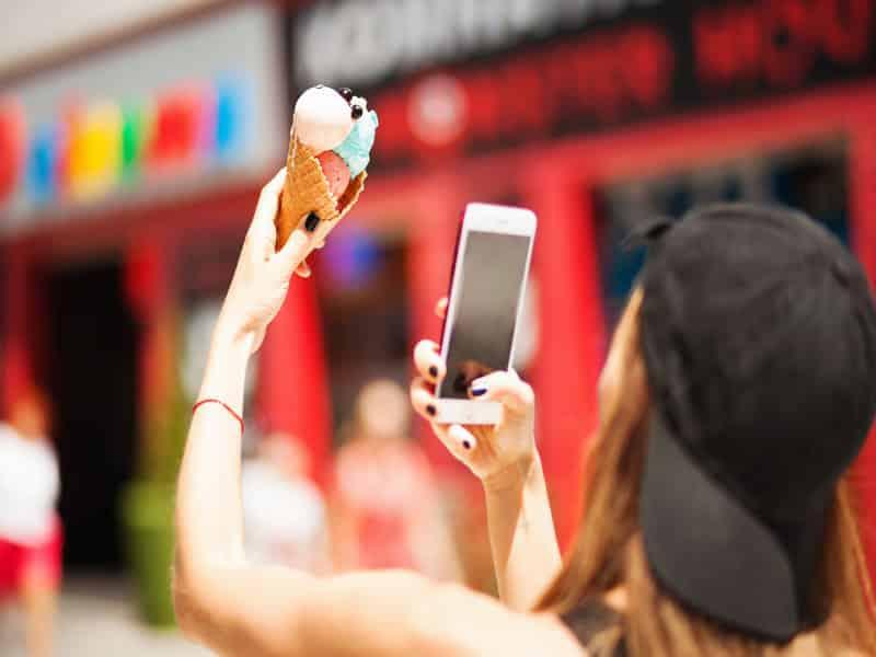 fille avec une casquette qui prend une photo de sa glace avec son smartphone pour instagram