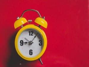 un réveil jaune à l'allure vintage sur fond rouge pour illustrer la question quand publier sur les réseaux sociaux