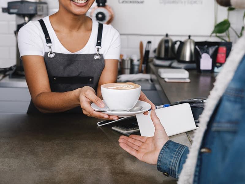 photo d'une serveuse tendant un café à un client par dessus un bar