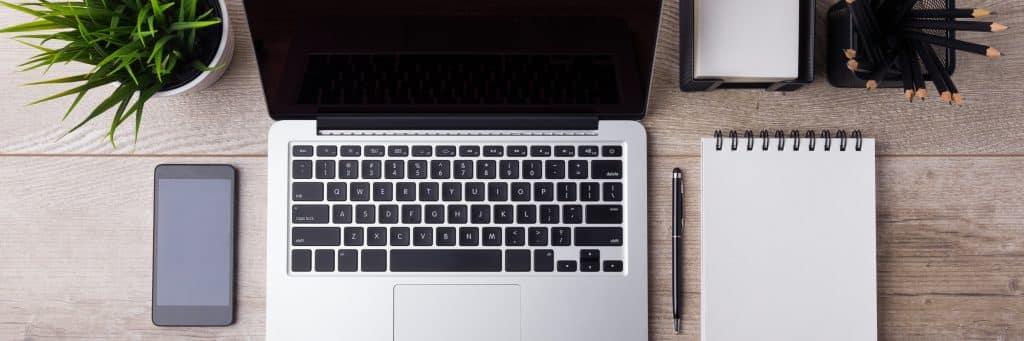 ordinateur portable très design photographié du dessus à côté d'un notebook et d'un smartphone