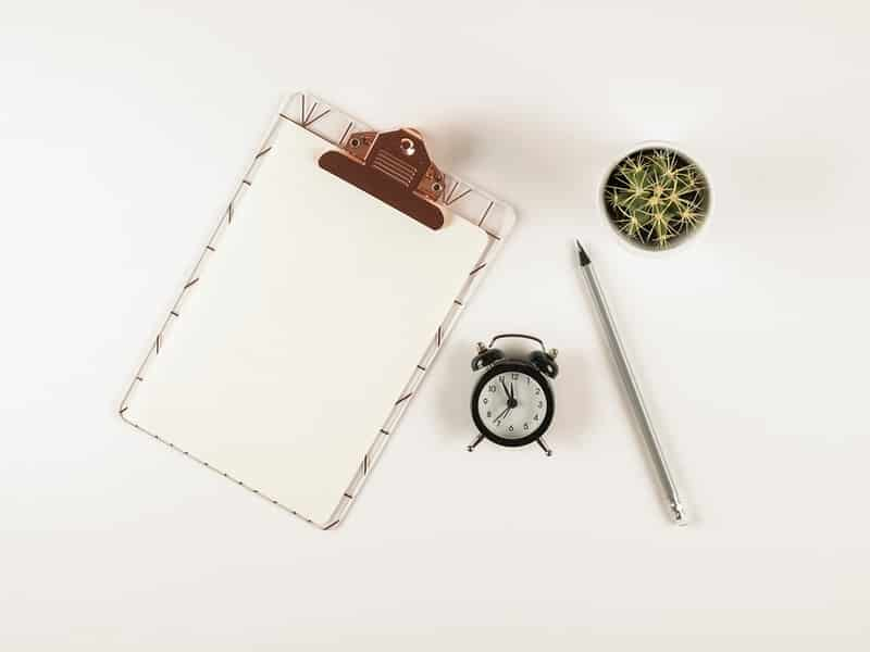 réveil, crayon, plante vert et calepin disposés sur un fond blanc