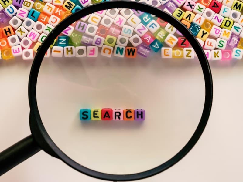 loupe grossissante qui pointent vers des petits cubes avec les lettres search pour désigner la recherche en ligne
