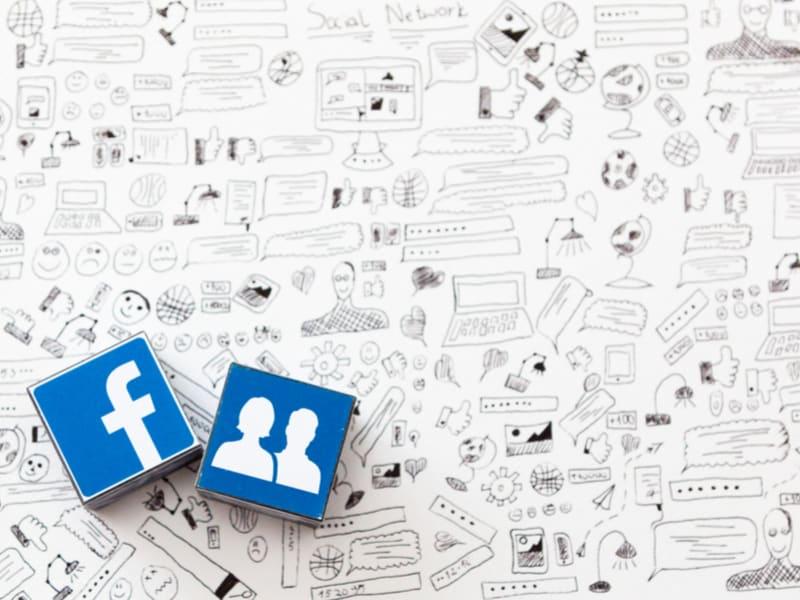cube avec deux logos facebook sur un fond blanc recouverts de dessins humoristiques