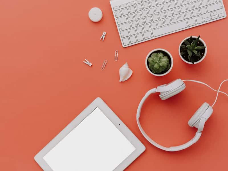 table orange samoné sur laquelle sont disposés un ordinateur une tablette et des écouteurs blancs à l'esprit très design