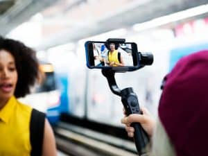 cameraman holding a smartphone on a selfie stick and shooting a woman with a yellow shirt