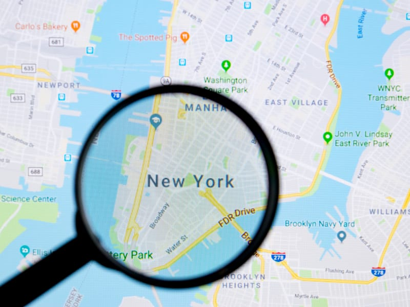 loupe grossissante pointant sur la ville de new york sur une carte google maps