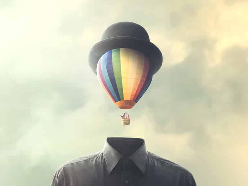 silhouette d'homme dont le visage est représenté par une montgolfière colorée s'envolant et surmontée d'un chapeau