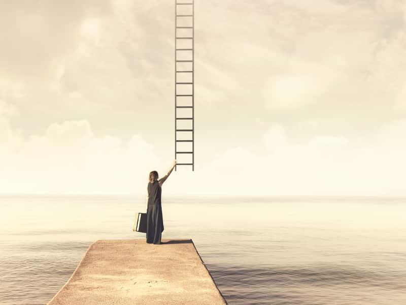 femme sur le point de grimper à une échelle qui monte dans le ciel