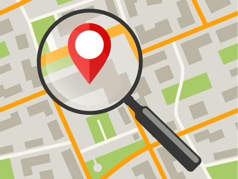 loupe grossissante qui zoome sur un repère de localisation google pour signaler un point sur une carte