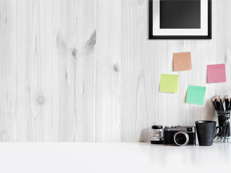 appareil photo sur une table devant un mur gris en planches surplombé de post it de couleurs