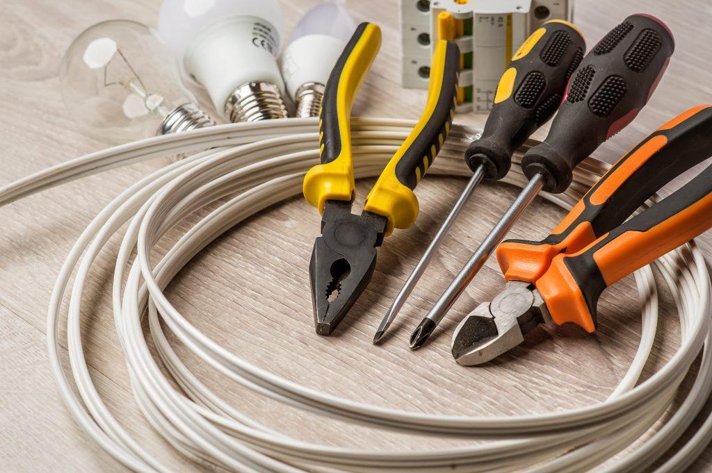 jeu d'outils de rénovation disposés sur un rouleau de fil électrique