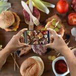 smartphone tenu par deux mains et prenant une photo de nourriture depuis le dessus