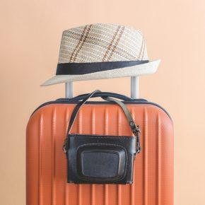 valise orange sur laquelle est posée un chapeau et un appareil photo