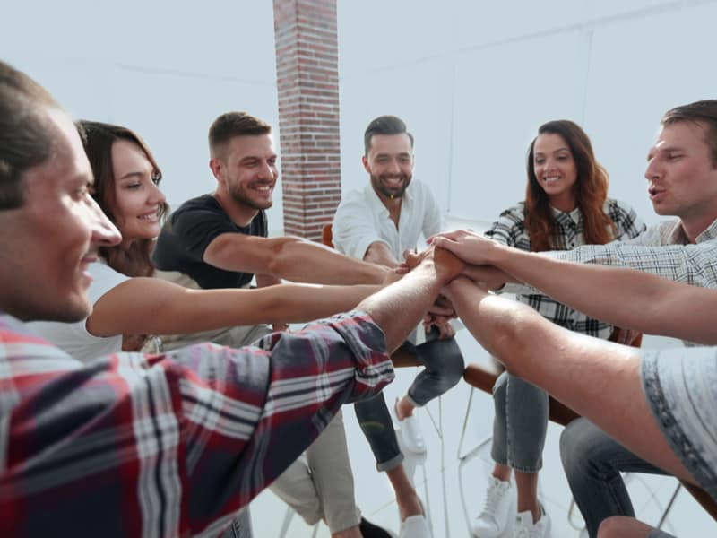 équipe d'employés les mains jointes dans le cadre d'une activité de team building