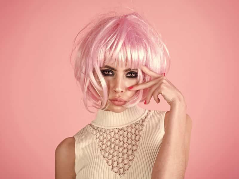 femme avec comme coiffure une perruque rose courte