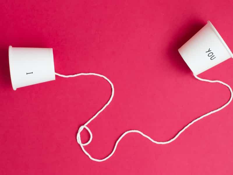 deux gobelets de plastiques avec les lettres toi et moi reliés par un fil