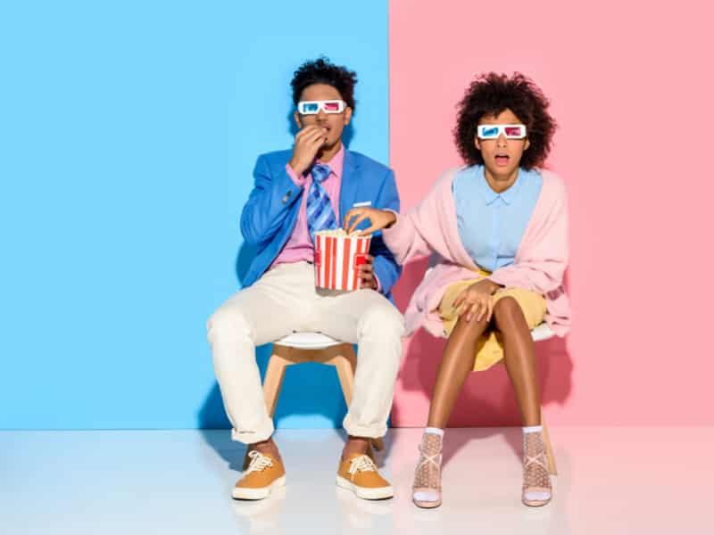 couple afroaméricain sur fond bleu et rose pastel qui regardent la télé en mangeant du pop corn