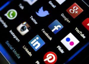 photo d'un écran de smartphone avec plusieurs applications de réseaux sociaux sur fond noir