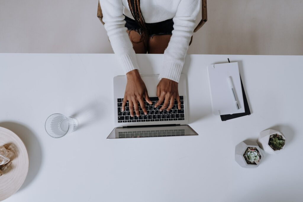 A woman using a laptop at a table. Photo by cottonbro from Pexels