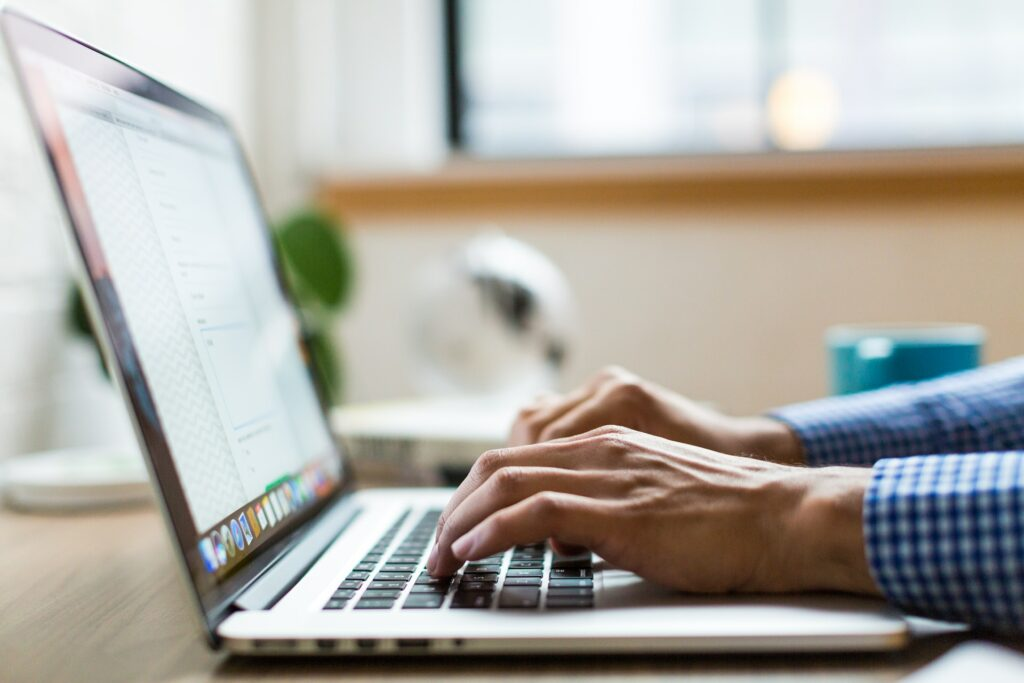 A person working to increase the online visibility of their small business on a laptop