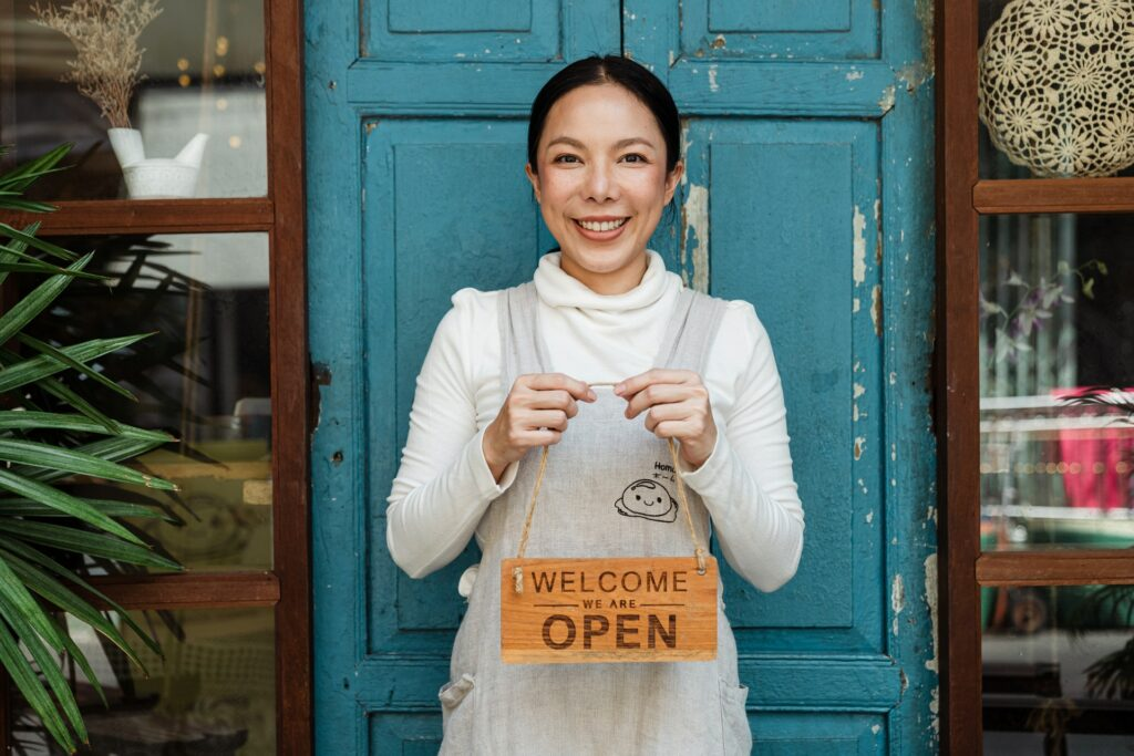 A business owner holding up a Welcome We Are Open Sign
