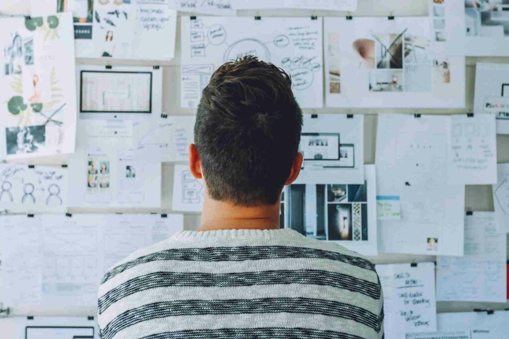 Man looking at a wall of keyword research ideas and suggestions