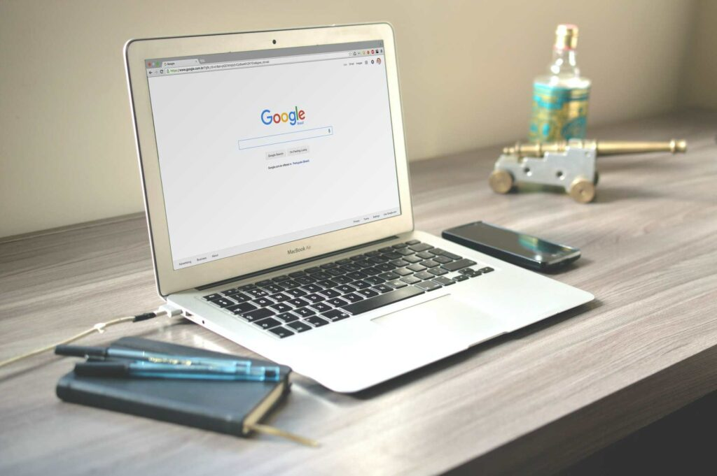 A laptop on a desk open to a blank Google Search