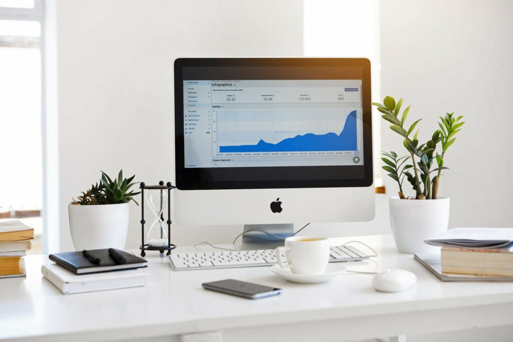 A computer on a desk showing a line graph depicting website traffic