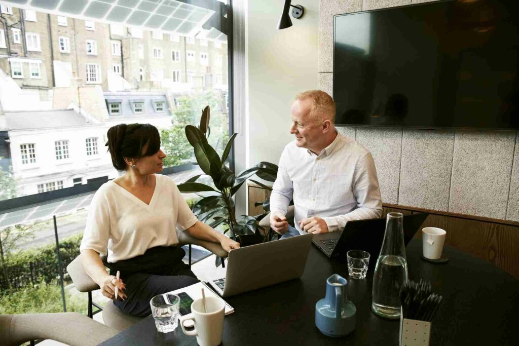A man and a woman in an office discussing their business.