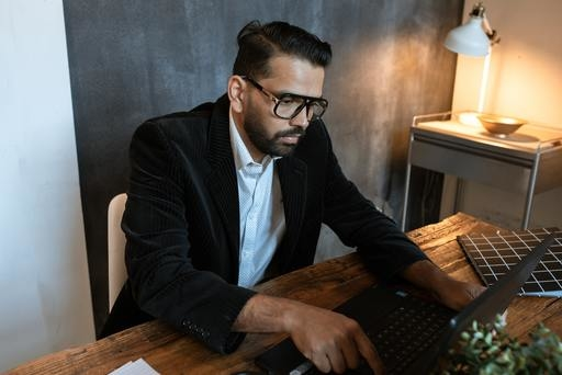 A businessman working on a laptop looking at creating a website