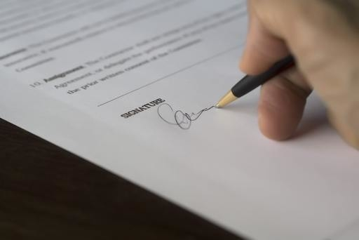 A person adding their signature to a document