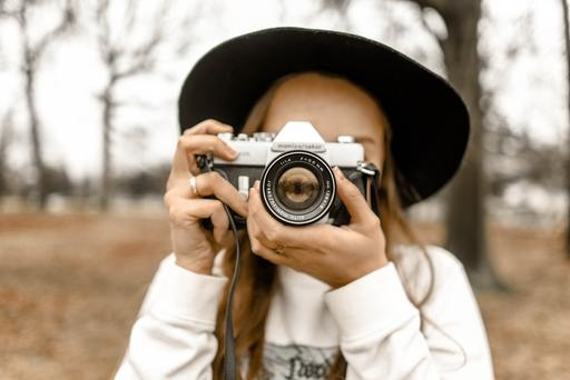 A woman using a camera in a field